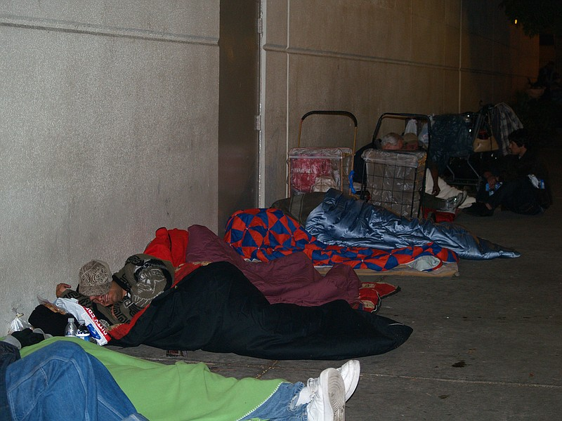 Homeless people bunker down for the night as early as 7 p.m. across the stree...