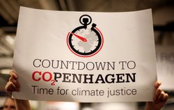 An environmentalist holds a banner reading 'Countdown to CO2PENHAGEN Time for climate justice' during the fourth day of the United Nations Climate Change Conference 2009 on December 10, 2009 in Copenhagen, Denmark.