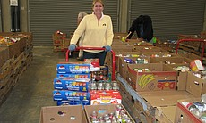 Volunteer Colleen Bethea selects food to be distributed at St. John's Catholic church in Encinitas. All of the food collected from red barrels goes into the selection that volunteers choose from.