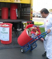A man loads barrels full of donated food onto a truck to take to the San Diego Food Bank.