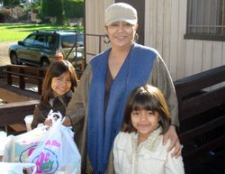 Irma Aguilar and her twin 8-year-old daughters, Karen (L) and Kathy (R) come to St. John's Catholic Church in Encinitas to pick up two bags of food on December 14, 2009.