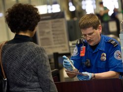 A TSA officer screens an airline passenger in Terminal C at Dallas/Fort Worth...