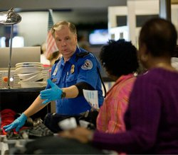 A TSA officer screens airline passengers at the Dallas-Fort Worth International Airport on Sunday. Pre-flight screenings were stepped up after a man was accused of trying to blow up a Northwest Airlines flight Friday.