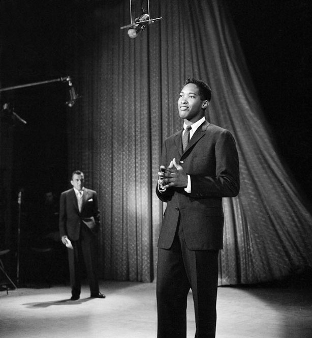 "Sam Cooke (foreground) put the spirit of the black church into popular music, creating a new American sound. Charming and brazen, Cooke had a silky voice and good looks that opened doors. The singer is shown here on stage with Ed Sullivan during an appearance on ""The Ed Sullivan Show,"" December 1, 1957."