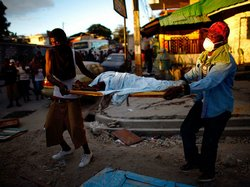 Haitian men carry the body of a child to a dump truck near downtown Port-au-P...