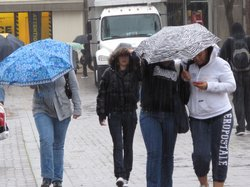 SDSU students take cover under their umbrellas as walk across campus on Janua...