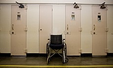 A wheelchair sits outside a prisoner's cell bec...