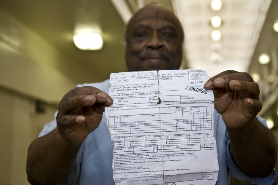 """Sullivan holds a crumpled, torn document indicating a DUI conviction. According to Sullivan, the DUI was his third strike, resulting in a sentence of 25 years to life. He says he served six years for murder in the 1960s, and a second sentence of 18 months for assault. Documents from the Department of Corrections indicate his third strike was a """"DUI/Bodily Injury"""" conviction. Sullivan says he'll be dead before he's eligible for parole."""