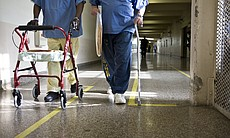 Two inmates walk together through the facility assisted by a walker and a cane.