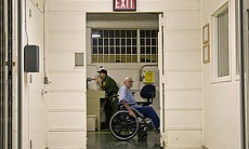 A prisoner in a wheelchair moves through the ha...