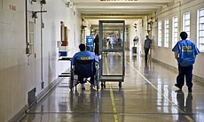 A wheelchair-bound prisoner pulls a laundry cart through the prison corridor ...