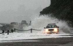 A wave crashes over a U.S. Park Police patrol car January 20, 2010 at Fort Point in San Francisco California.