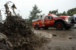 Firefighters pass fast-moving muddy water during the fourth storm of the week...