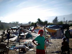 A woman stands near a makeshift refugee camp near downtown Port-au-Prince on Jan. 16. The government is now planning to relocate many survivors to formal camps on the outskirts of town.
