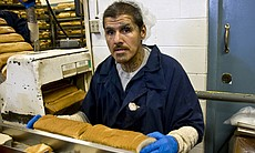 Daniel Ayala is serving a three year sentence. He monitors a machine that slices up loaves of bread for use in the inmate lunches.