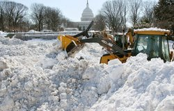 A front end loader piles up snow that was trucked in from Senate parking lots at the U.S. Capitol on February 8, 2010 in Washington, DC.