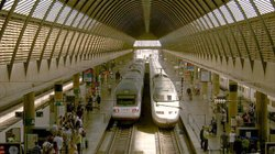 In Madrid, passengers wait to board a high-speed train. For nearly 20 years, ...