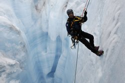 James Balog rappelling down moulin, Ice Sheet, Greenland.