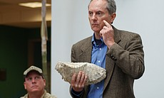 Dr. Thomas Deméré, Curator of Paleontology at the San Diego Natural History Museum, presents a fossil of a mammoth molar found in the East Village. Behind him sits the lead field paleontologist on the project, Pat Sena. The Natural History Museum presented the fossils, including a mammoth and a gray whale, on February 17, 2010.