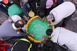 People fill bottles of water from an inflatable pool outside of a fire station in Concepcion on March 1, 2010.