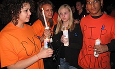Chelsea King's friends, (left to right: Britnee Kaminski, Bryanna Hauser, Breanna Halpin and Abdullah Ziyada) wear the color orange at a candlelight vigil in her memory because they say the color reflects King's bright, energetic and radiant personality, March 2, 2010.