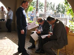 Iraqi expatriates fill out the appropriate forms required to cast their vote ...