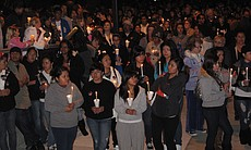 A crowd listens to family tributes during a candlelight vigil in memory of 14...