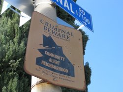 A Neighborhood Watch sign greets visitors on a residential sidewalk in Poway.