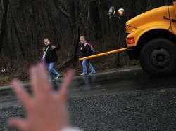 Kristy Stumpf, who works from her home in Broad Run, Va., part of the week, greets her daughters Lauren, 9 (left), and Lacey, 6 (right), as they hop off the school bus. Stumpf's employer, List Innovative Solutions, lets employees largely set their own hours