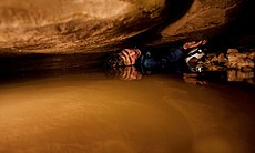 Prime qualification for cavers: tolerance for a tight squeeze. John Benson can make progress only with his helmet off and his head turned just so. He exhales, making his body as flat as possible, slides a few inches on his back, stops, inhales and repeats. Photo by Stephen Alvarez published in National Geographic Magazine, June 2009.