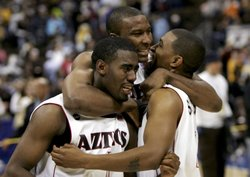 Marcus Slaughter #42 hugs Brandon Heath #1 and John Sharper #15 of the San Diego State University Aztecs after defeating the Wyoming Cowboys 69-64 in the championship of the Mountain West Conference Basketball Tournament on March 11, 2006 at the Pepsi Center in Denver, Colorado.