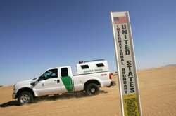 A border patrol vehicle passes an international border marker in the Colorado Desert at the Imperial Sand Dunes, also known as the Algodones Dunes, along the U.S.-Mexico border on April 5, 2008 between El Centro, California and Yuma, Arizona.