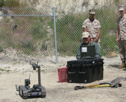 "Aaron Pluff manoevers a ""Pack Bot"" Robot to identify and disarm an IED at training at Camp Pendleton."