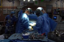 Dr. Leonard Bailey (center) performs pediatric heart transplant surgery at Lo...