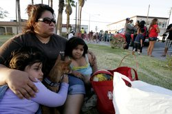 Ana Velazquez and her daughter Mariana and Angelica, sit on the grass after crossing the border into the U.S. after a 7.2 magnitude earthquake struck the area April 4, 2010 in Calexico, California.