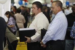 People line up to speak with prospective employers during the Arizona Workfor...