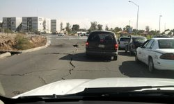 Cracked asphalt near the zoo off De Los Presidentes in Mexicali. The building...