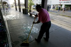 A man sweeps up broken glass after a 7.2 magnitude earthquake struck the area April 4, 2010 in Calexico, California.
