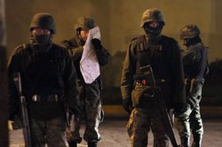Members of the Mexican Army study a map at an early morning murder, one of numerous murders over a 24 hour period, on March 26, 2010 in Juarez, Mexico.