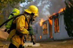 US forestry firefighter pulls a hose to a burning home in Deerhorn Valley as the Harris Fire continues growing beyond 70,000 acres on October 24, 2007 near Jamul, California.