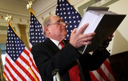 Holding a stack of evidentiary papers, Sen. Carl Levin (D-MI) answers questio...