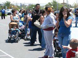 A line of parents wait on the playground of Rodriguez Elementary School on Wednesday May 12, 2010, to enroll in the federal food stamp program.