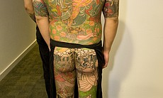 A model with a full body tattoo waits to go out on the runway.