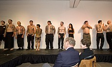 The tattooed models line up after the runway show as museum patrons look on.
