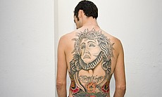 James Cooley shows off his back tattoo.