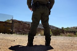 A U.S. Border Patrol agent stands near the border fence in Nogales, Arizona, May 2, 2010.