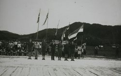 British Major Tom Harrisson and some of his Australian commandoes on the bamboo airstrip in June, 1945. Harrisson and his men launched an audacious rescue plan to get the U.S. airmen out of Borneo. To the right of the flagpoles is the head of a senior Japanese official, brought to Harrisson as a gift from one of the local headmen.