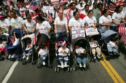 Mothers with babies in strollers join the march to City Hall in one of severa...