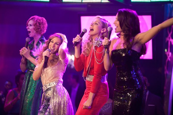 "Cynthia Nixon, Sarah Jessica Parker, Kim Catrall and Kristin Davis belt out ""I am Woman"" to inspire the locals."