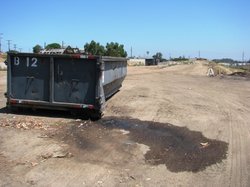 Trash trucks dump their loads in this dusty lot in National City. Local officials plan to convert this brownfield into a site for eco-friendly, low-income housing with green space and a community garden.